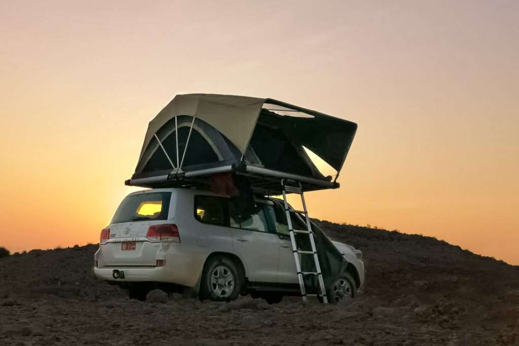 Cruiser with rooftop tent in sunset oman